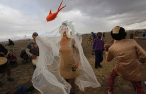 Festivalgoers dance during a dust storm at the start of the AfrikaBurn festival