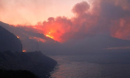 A wind-driven wildfire rages along the California coast