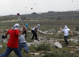 Palestinians throw stones during clashes with Israeli settlers in Deir Jarir, West Bank