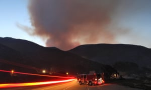 A fire engine is parked on Pacific Coast Highway as the Springs Fire continues to burn in the hills at Point Mugu State Park