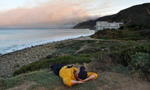 A firefighter sleeps on a bluff as the Springs Fire burns in the early morning near Pacific Coast Highway