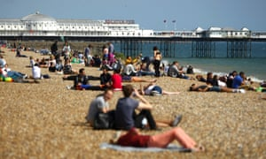 People relax on the beach in front of Brighton Pier in the warm and sunny weather today which is set to continue throughout the bank holiday weekend.