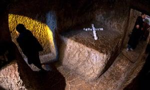 A Greek Orthodox woman leaves an underground walkway cut through stone inside the Partorium Church in Jerusalem.