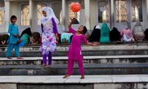 Kashmiri Muslim girls play as women in background pray at Hazratbal Shrine on the outskirts of Srinagar, India.