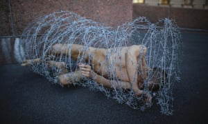 Artist Pyotr Pavlensky lies on the ground, wrapped in barbed wire roll, during a protest action in St. Petersburg.