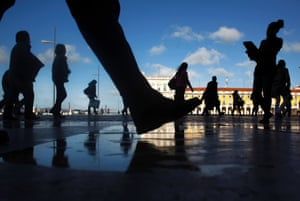 Commuters walk along Comercio square during a 24-hour subway workers strike, Lisbon, Thursday, May 30, 2013.