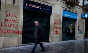 -- A man walks next to the Banco Sabadell, with graffiti: Today all the streets to fight and thieves.