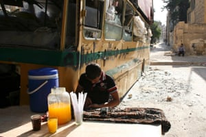 A boy sells juice next to a damaged bus in Aleppo's Bustan al-Qasr district