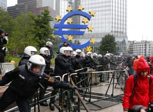 German police officers stand behind metal barricades during a demonstration of some hundred anti-capitalism Blockupy protesters in front of the European Central Bank in Frankfurt, Friday, May 31, 2013.