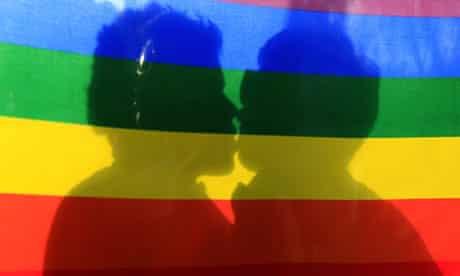 Couple kissing behind rainbow flag