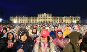 Slightly soggy people attend the Vienna Philharmonic summer open air concert conducted by US conductor Lorin Maazel, at the Schonbrunn Palace in Vienna, Austria, on a rainy evening yesterday.