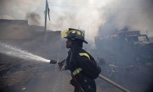 A firefighter works to extinguish a massive fire at Port Market in Port-au-Prince, Haiti. The building caught fire on Thursday, spreading to a market next door, and injured at least 30 people.