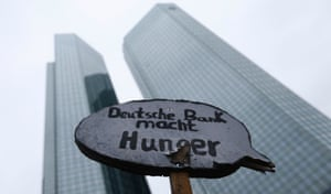 """A protestor holds a placard reading """"Deutsche Bank causes hunger"""" in front of the headquarters of Germany's largest business bank, Deutsche Bank AG, during an anti-capitalism """"Blockupy"""" demonstration in Frankfurt, May 31, 2013."""