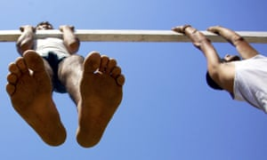 Other candidates perform chin-ups as part of a physical fitness test. Photographs: Jaipal Singh/EPA