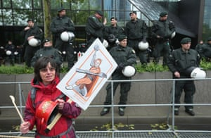 A protester bangs on a pot to protest against speculation in world food prices by Deutsche Bank outside Deutsche Bank headquarters as riot police look on during Blockupy protests on May 31, 2013 in Frankfurt am Main, Germany.