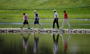 Fore/four! Golfers Roope Kakko (red top) of Finland and Mark Foster (white top) of England and their caddies on the 17th hole during the Nordea Scandinavian Masters at Bro Hof Slott Golf Club in Stockholm, Sweden.