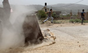 Palestinian protesters run away from an approaching Israeli army bulldozer during clashes at the weekly protest against the Jewish settlement of Qadomem, at Kufr Qadom village near Nablus, West Bank. At least 15 Palestinians were wounded during the clashes.