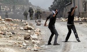 Protesters hurl stones at Israeli soldiers. Photographs: Alaa Badarneh/EPA