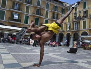 A Brazilian artist performs capoeira at Plaza Mayor square in Palma de Mallorca.