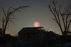20 Photos: fireworks explode far above a house damaged by a tornado in Moore, Oklahoma