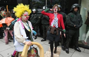 Riot police look on as Blockupy protesters dressed as clowns demonstrate against the exploitation of textile workers in Frankfurt's Zeil pedestrian shopping street.