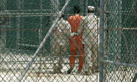 Prisoner at Guantánamo Bay is escorted by guards