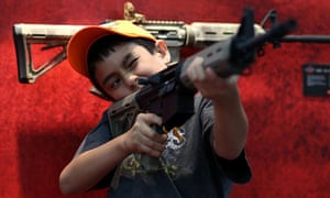 A young attendee inspects an assault rifle during the NRA Annual Meeting in Houston, Texas