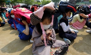 South Korean school children, with schoolbags on their heads, take shelter on the ground during an earthquake drill in Seoul, South Korea. Students throughout the country practiced drills ranging from fire to terror attacks and earthquake as part of an annual event called a Safe Korea Exercise.