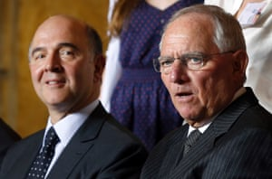 German Finance Minister Wolfgang Schaeuble, right, speaks as he poses for a family photo with his counterpart from France, Pierre Moscovici, left, as part of the 25th meeting of the German French Finance and Economy Council in Berlin, Germany, Tuesday, May 7, 2013.