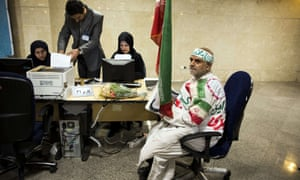 Ali Nassiri, wearing a shroud and holding the national flag, registers his candidacy for the upcoming presidential election at the interior ministry in Tehran, Iran.
