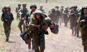 An Israeli soldier carries another soldier as they walk with their comrades during training close to the ceasefire line between Israel and Syria in the Israeli occupied Golan Heights.