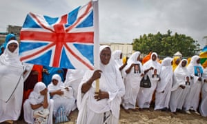 A Somali woman carries a Union flag during a demonstration taking place in Mogadishu in support of the international donors' conference taking place in London. Somali President Hassan Sheikh Mohamud opened the international conference by asking donors to provide 'considerable investment and support' for his beleaguered government in the coming years.