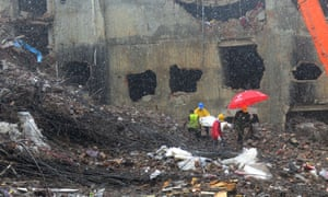 Bangladeshi rescue personnel carry stretchers with the remains of garment workers from the site of a collapsed building as heavy machinery clear the debris in Savar on the outskirts of Dhaka.