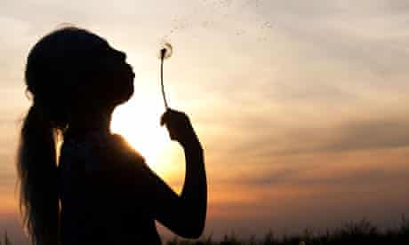 Silhouette of a girl blowing dandelion
