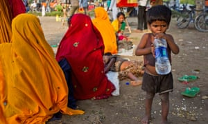 Thirsty work for some. An Indian boy drinks water on a hot summer day, as his family of trinket sellers rest nearby in New Delhi, India.