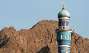 A minaret cast against the mountains in Oman