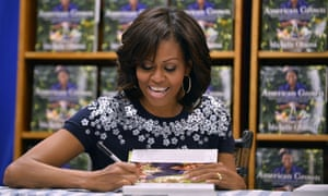 US First Lady Michelle Obama signs a copy of her book 'American Grown: The Story of the White House Kitchen Garden and Gardens Across America,' during a book signing event at Politics & Prose in Washington, DC.