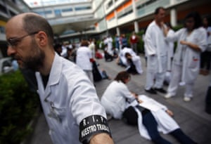 """A health worker wearing a black armband which reads, """"R.I.P. our job"""", joins others as they perform mock doctor consultation sessions during a protest against the local government's plans to cut public healthcare spending outside Infanta Leonor hospital in Madrid May 7, 2013."""