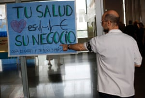 """A health worker wearing a black armband which reads, """"R.I.P. our job"""", points at a sign during a protest against the local government's plans to cut public healthcare spending outside Infanta Leonor hospital in Madrid May 7, 2013. The sign reads, """"Your health is their business."""""""
