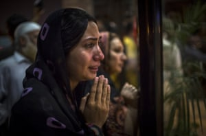 A woman believed to be a family member clasps her hands in prayer as people gather at the front doors of the Shaukat Khanum Memorial Cancer Hospital and Research Centre waiting to hear news of the medical condition of Imran Khan, chairman of the Pakistan Tehrik e Insaf (PTI) party, who was injured falling off a lifter during an election campaign rally in Lahore, Pakistan.