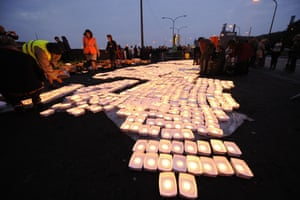 A collective of artists from Liege light candles before placing them into a river as they take part in a solidarity action for workers of the ArcelorMittal steel plant near a bridge in Sclessin. Twelve thousand floating candles were lit to symbolize the loss of jobs which will follow the closure of the ArcelorMittal site.