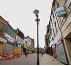 Virtually deserted high street with boarded up shops