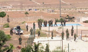 Forces loyal to Syria's President Bashar al-Assad stand near an empty swimming pool during what they said was a military operation against rebels in the al-Mansoura area near Aleppo.