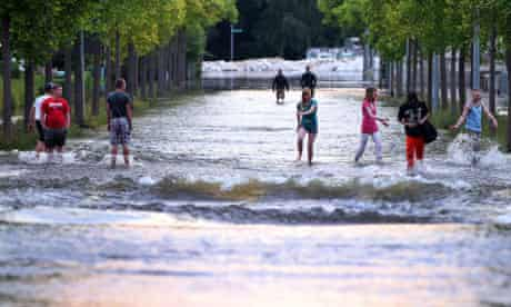 Pedestrians walk through a street flooded by the river Elbe, in Magdeburg, Germany