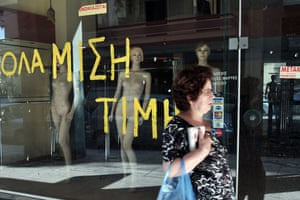 A woman walks past a shut down store in Athens bearing an old announcement 'everything at half price'  and a 'to rent' sign on June 10, 2013.