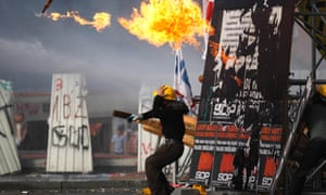 A protester throws a petrol bomb towards riot policemen during clashes in Taksim Square in Istanbul, Turkey.  Hundreds of police in riot gear forced through barricades in Istanbul's central Taksim Square early Tuesday, pushing many of the protesters who had occupied the square for more than a week into a nearby park.