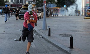 A protester runs as Turkish riot police fire water cannon and teargas during a protest at Taksim Square in Istanbul on 11 June.