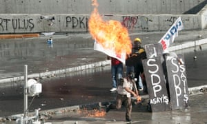 A petrol bomb is thrown at riot police in Taksim Square in Istanbul on Tuesday.