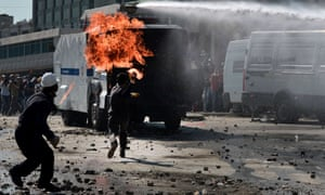 Men throw petrol bombs at police vehicles in Istanbul's Taksim square on 11 June.