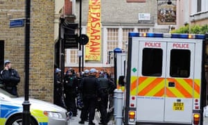 Riot police officers surround a building in Beak Street